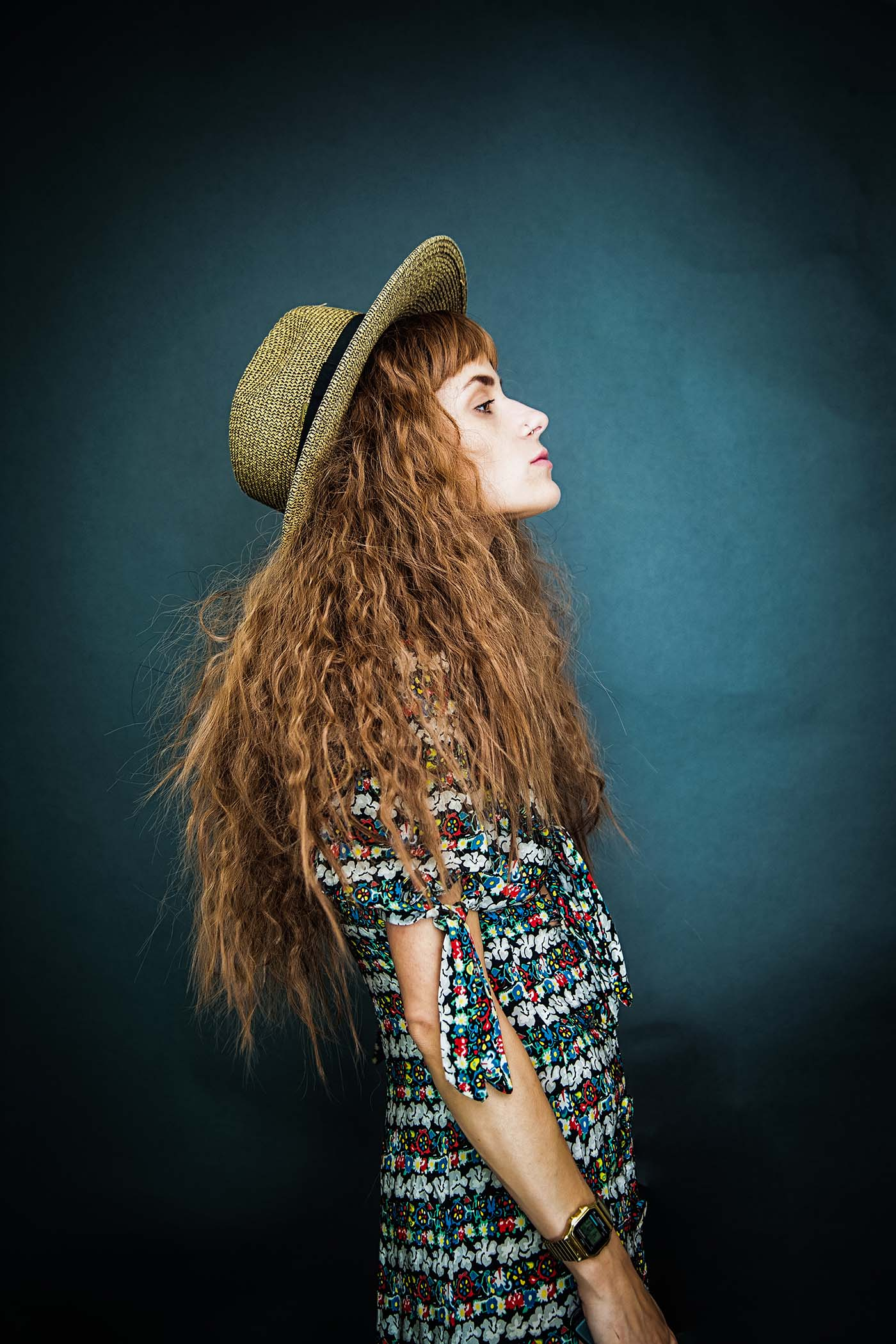 Fashion Photography: Woman in hat against a blue backdrop.
